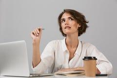 严肃女商人摆在被隔绝在坐在桌上的灰色墙壁背景使用膝上型计算机 免版税库存照片