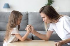 严肃妈妈和孩子女儿武器角力有交锋 免版税库存图片