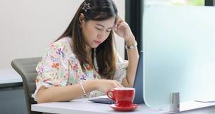 严肃对工作和使用笔记本的亚裔女实业家为谈论的商务伙伴文件和想法在见面 免版税图库摄影