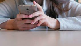 严肃年轻人妇女读书某事在她的坐在咖啡馆的手机 特写镜头手 股票录像