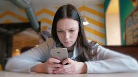 严肃年轻人妇女读书某事在她的坐在咖啡馆的手机 股票视频