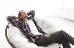 严肃的人休息坐和作梦在一把大舒适的椅子 库存图片