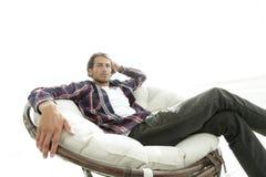 严肃的人休息坐在一把大舒适的椅子 侧视图 免版税库存照片
