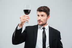 严肃的人斟酒服务员在品尝在玻璃的随员红葡萄酒 图库摄影