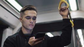 严肃的人画象拿着在公共交通工具的扶手栏杆浏览智能手机 股票录像