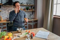 严肃的人立场在厨房里在桌上 他在电话nad谈话认为 被打开的说谎在桌上的菜谱和菜 免版税图库摄影
