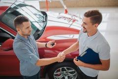 严肃的人站立并且互相震动` s手 采购员把握汽车关键 Dealler举行片剂 他们做了一个成交 红色汽车 库存图片