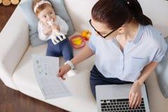 严肃的企业夫人坐有她的孩子的一个长沙发 免版税库存照片