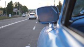 严肃的公司机在移动的减速火箭的汽车的左边镜子被反射 驾驶一辆蓝色葡萄酒汽车的年轻人  影视素材