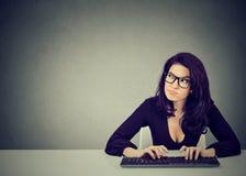 严肃的出神的少妇在键入的书桌坐桌面的键盘 免版税库存图片