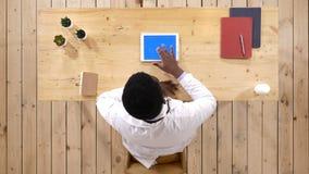 严肃的医生与一台片剂计算机一起使用在他的猛击页的办公室 蓝色屏幕大模型显示 股票视频
