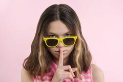 严肃的十几岁的女孩在明亮的黄色玻璃的13,14年炫耀沈默标志 免版税库存图片