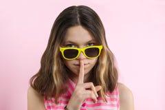 严肃的十几岁的女孩在明亮的黄色玻璃的13,14年炫耀沈默标志,保留在嘴唇的前面手指,桃红色演播室背景 库存图片