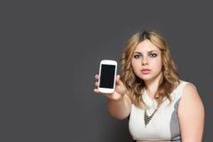 严肃的十几岁的女孩显示巧妙的电话 免版税图库摄影