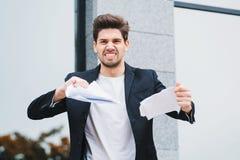 严肃的在片断的商人撕毁的合同 投掷压皱纸的恼怒的愤怒的男性办公室工作者,有紧张 免版税库存图片