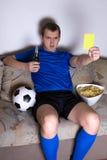 严肃的在电视的人观看的橄榄球在家和显示黄色c 免版税库存照片