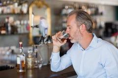 严肃的在酒吧柜台的人饮用的威士忌酒 库存照片