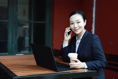 严肃的女商人美丽的年轻白肤金发的妇女谈话在研究一台膝上型计算机个人计算机计算机的流动手机在餐馆 免版税库存照片