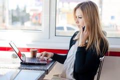 严肃的女商人美丽的年轻白肤金发的妇女谈话在研究一台膝上型计算机个人计算机计算机的流动手机在餐馆 免版税库存图片