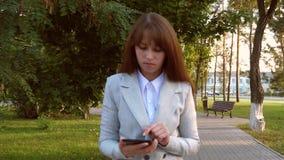 严肃的女孩商人沿胡同在手中走在有片剂的公园 轻的西装的妇女检查电子邮件  影视素材