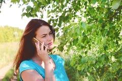 严肃的女孩谈话在电话反对自然背景 免版税库存图片