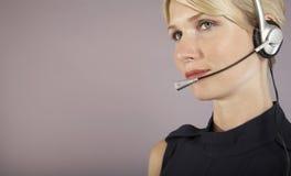 严肃的女实业家佩带的耳机 免版税库存照片