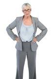 严肃的女实业家用她的在臀部的手 库存照片