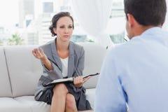 严肃的女实业家谈话与她的同事 免版税库存照片