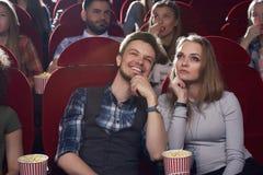 严肃的妇女和微笑的人观看的电影在现代戏院 库存图片