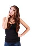 年轻严肃的妇女扶植下巴并且看  免版税库存图片