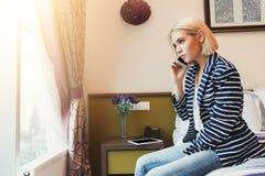 严肃的妇女谈话在电话在旅馆客房 免版税库存图片