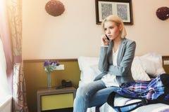 严肃的妇女谈话在电话在旅馆客房 免版税图库摄影