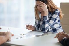 严肃的妻子签署的离婚旨令在律师事务所 免版税图库摄影