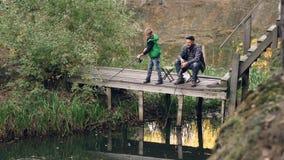 严肃的孩子在木码头站立并且钓鱼拿着标尺,当他爱恋的父亲坐椅子时,捉住 影视素材