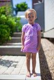 严肃的小女孩在她的家前面站立 库存照片
