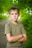 严肃的小男孩特写镜头画象有被折叠的手outdoo的 库存图片