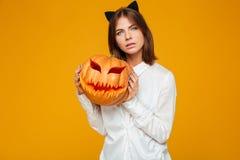 严肃的少妇在疯狂的猫万圣夜服装穿戴了 免版税图库摄影