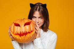 严肃的少妇在疯狂的猫万圣夜服装穿戴了 库存照片