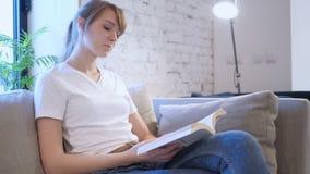 严肃的少妇阅读书,在沙发的开会 股票视频