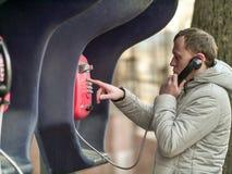 严肃的年轻人叫由红色街道投币式公用电话 库存照片