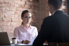 严肃的年轻人HR经理妇女采访的男性候选人 免版税库存图片