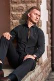 严肃的年轻商人佩带的T恤杉和黑长裤有蓝眼睛的 免版税库存照片