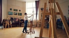 严肃的年轻女人艺术家工作在与丙烯酸漆的图片绘画在艺术有画架的学校教室和 股票录像