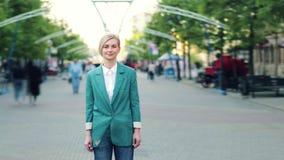 严肃的年轻女人身分时间间隔画象在城市街道的在人群中 股票视频