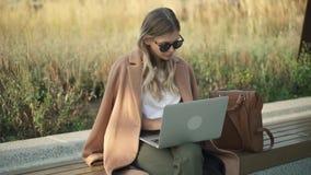 严肃的年轻女实业家与她的膝上型计算机一起使用外面在秋天天 股票视频