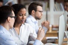 严肃的年轻非裔美国人的妇女谈话与同事 免版税库存图片