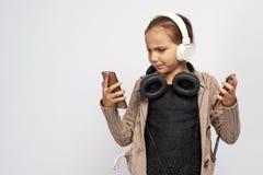 严肃的恼怒的女孩在温暖的夹克穿戴了,一起按她的嘴唇并且剧烈地凝视电话,皱眉充满不快 免版税库存图片
