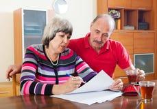 严肃的成熟夫妇读书文件 免版税图库摄影
