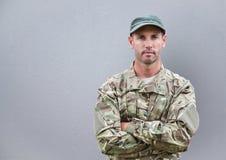 严肃的战士用他的被折叠的手 后边混凝土墙 图库摄影