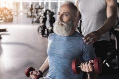 严肃的有胡子的领抚恤金者在运动中心做着锻炼 免版税库存照片